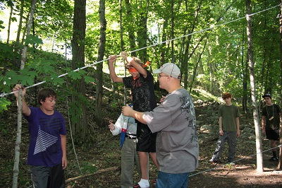 Campers using the low ropes Trust Course