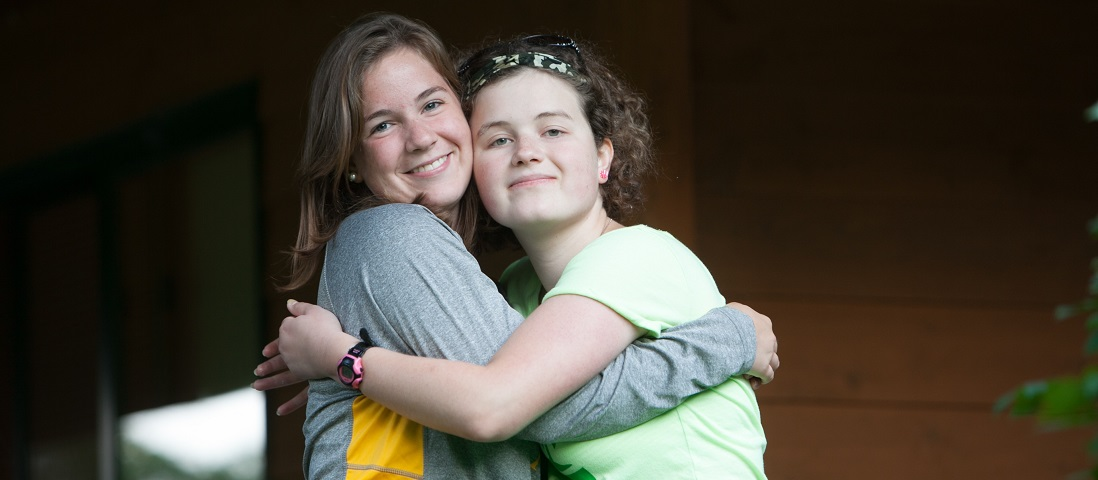Camp counselor and camper hugging on deck.