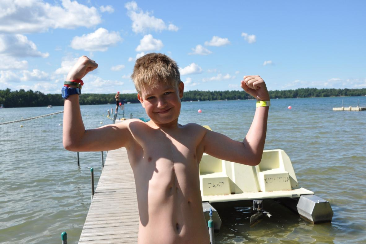 Camper showing his muscles on the dock.
