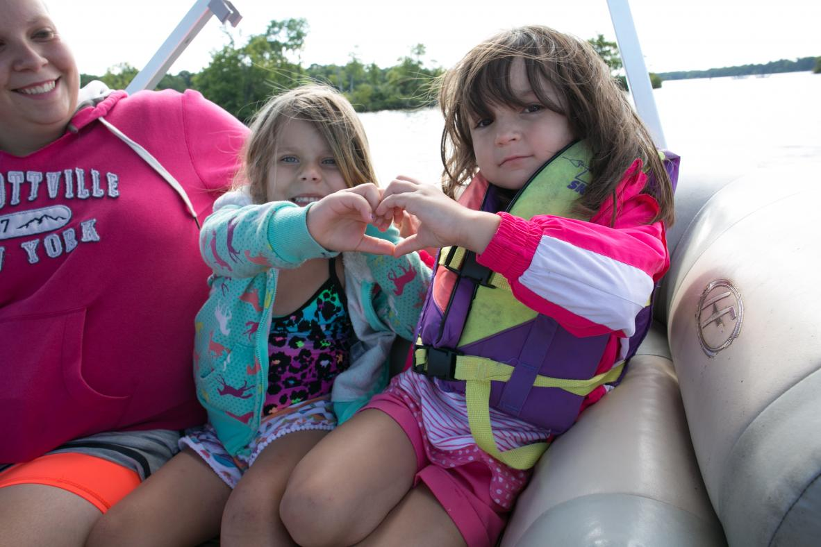 Friends making a heart with their hands on a boat.