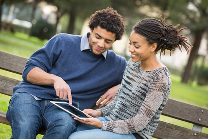 couple on bench with ipad