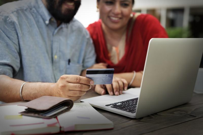 Couple holding a credit card and using a laptop