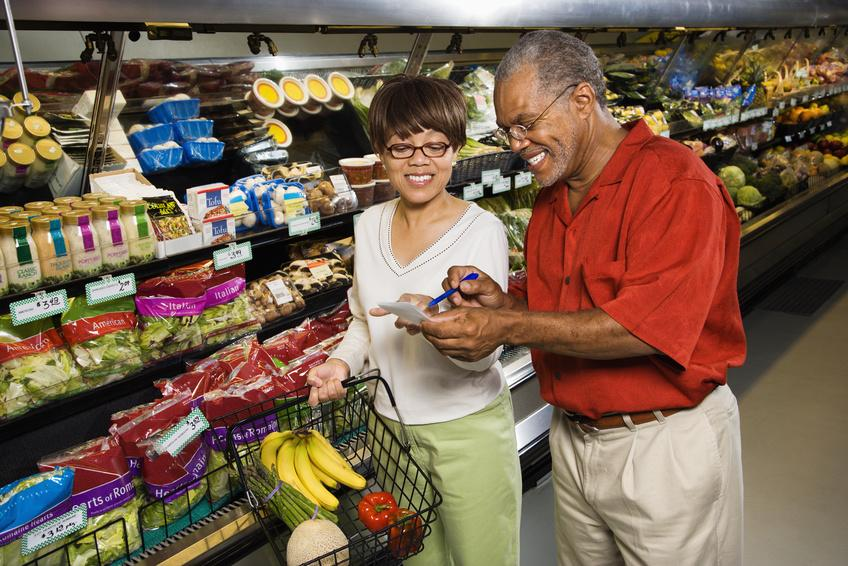 Couple look over grocery list in produce section of store