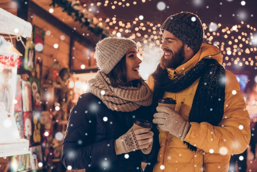 Smiling couple in holiday scene outside holding warm beverages