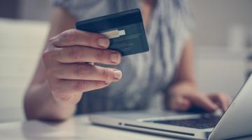 Woman at laptop with credit card in hand
