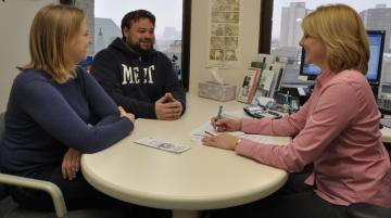 Young woman and man meeting with middle aged woman about finances
