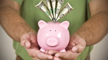 Man's holding a pink piggy bank with bills sticking out of the coin hole