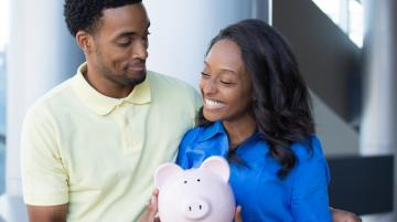 Young African-American couple holding piggy bank and smiling