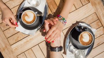 Couple holding hands and drinking coffee