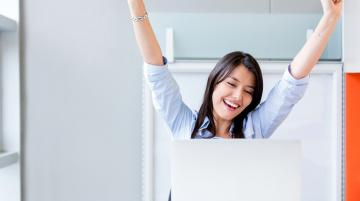 Woman celebrating at her computer