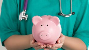 doctor holding a piggy bank