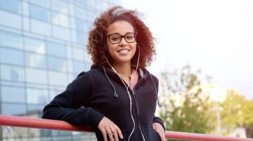 Young person of color smiling and listening to mobile device