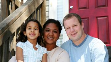 Multiracial family sitting on front steps of house