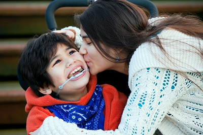 Woman kissing boy in wheelchair