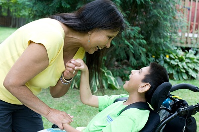 Woman holding the hand of a boy with a disability.