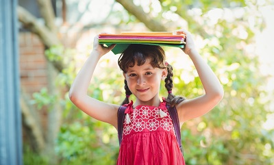 Girl carrying binders on her head.