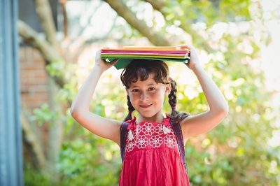 Girl holding books on top of her head.