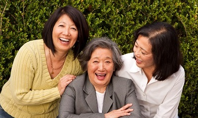 A mother and two daughters laughing.