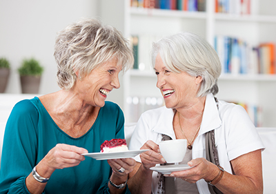 Two women laughing, eating cheesecake