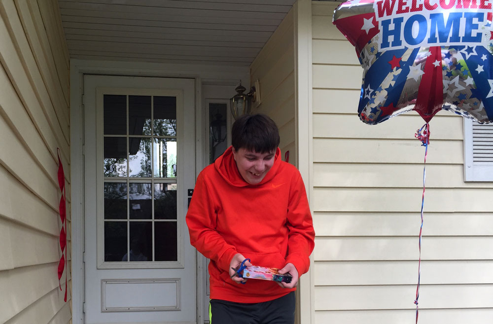 Individual in front of house with welcome home balloon