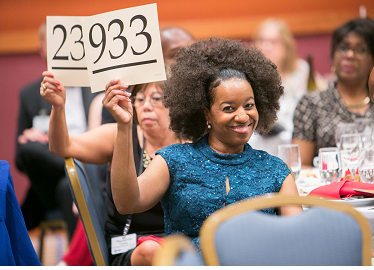 Photo of a woman bidding at an event auction.