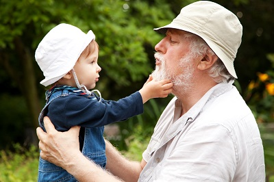 Child playing with elderly man's beard.