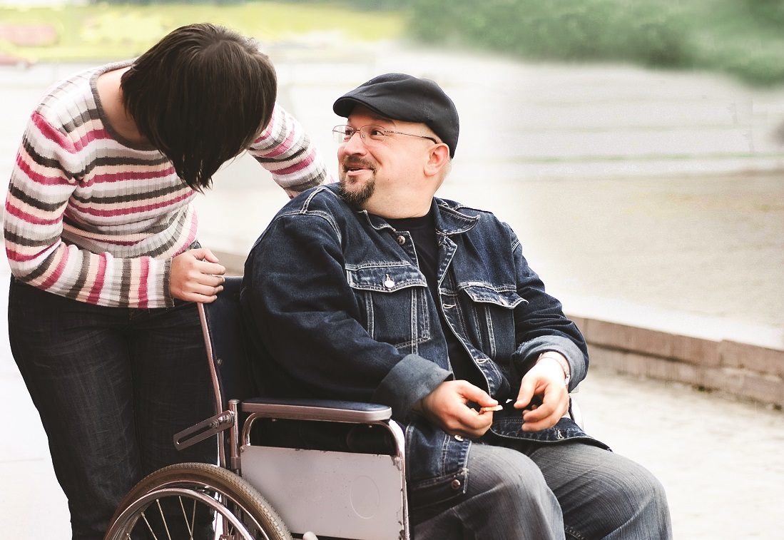 woman smiling at man in wheelchair