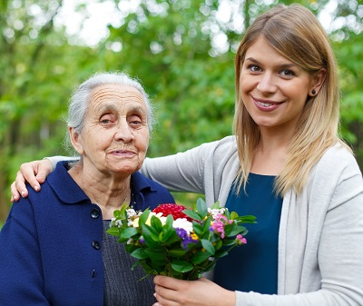 Older woman and younger woman posing with flowers
