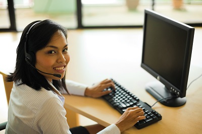 woman wearing headset at a computer