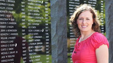 Therapist and veteran Jolaina Falkenstein next to a war memorial
