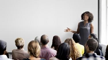 photo of a woman instructing a group of adults.